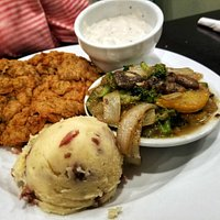 Country fried steak with mixed vegetables and mashed potatoes.