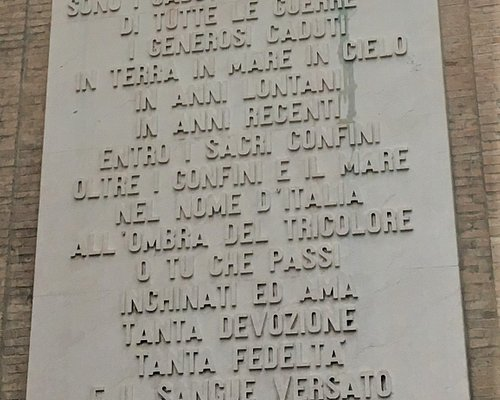 Memorial to all wars on a large white Verona marble plaque, with inscription, and five heads crowned with barbed wire.