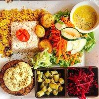 O famoso hambúrguer de lentilha ao molho de abacate e ervas finas. Farofa artesanal, arroz integral com açafrão, batatas rústicas assadas, molho de manga e maracujá e saladas variadas.