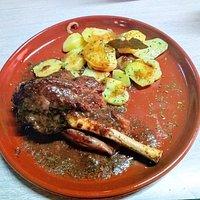 Jarret de Xai cuinat a baixa temperatura 36h amb una salsa de reducció de carn amb patates i ceba al forn
