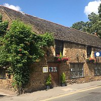 The exterior of Hitchen's Barn showcasing the beautiful trumpet vine.