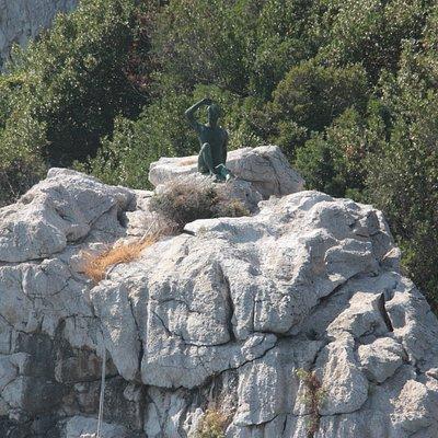 Vista de frente de la escultura encima de un promontorio.