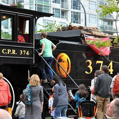 Climb aboard! Enthusiastic visitors climb into the Engine 374 cab which makes its annual pilgrimage onto the Roundhouse Turntable Plaza to celebrate its arrival in Vancouver on May 23, 1887. Photo by Barbarah Senez, 2013.