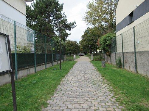 Vue depuis la rue, portail d'entrée et fresque sur le pilier gauche
