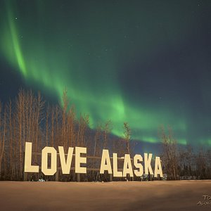 "Beautiful Aurora dancing over our unique ""Love Alaska"" sign!"