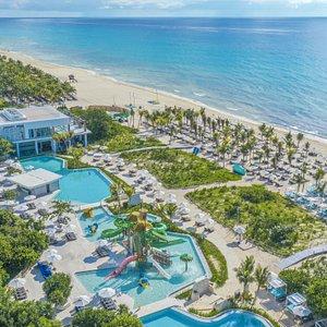 Nuestra nueva piscina frente al mar con todas las comodidades para tu familia como snack bar, camastros e incluso un parque acuático te encantará