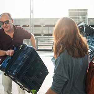 driver helps young woman unload her bags.