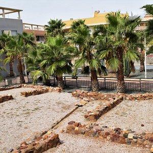 Palm trees line one end of the roman ruins of Casa Romana de la Calle Era