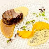 Medallón de ciervo a la brasa con salsa de la pasión y reducción de naranja con puré de patatas al estilo emociones.