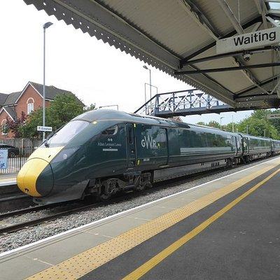 A mainline train departs from Evesham Railway Station.
