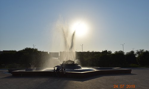 sun setting in the background of fountain