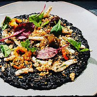 Squid ink risotto, marinated peppers, squid and bread crumbles