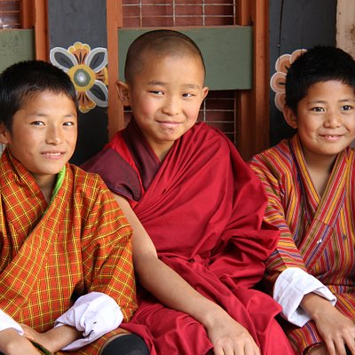 A young novice monk waiting to get enrolled into the monastic school with his two friends who came to see him off.