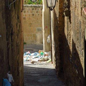 spazzatura ammucchiata in fondo ad un vicolo