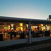 Open restaurant filled with people and a nice atmosphere.It has a lawn for the kids to play whilst having your meal and 30m from the beach.