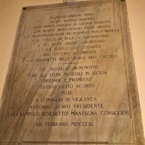 """Nell'ingresso, una lapide del 1890, regnante Umberto I, ricorda come il Regio Conservatorio si aprisse in quella data """"agli esterni"""" e """"alle giovinette della divina arte cultrici""""."""