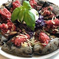 Pizza gourmet, impasto al carbone vegetale con tartare di scottona, cappuccio viola, burrata e scaglie di grana.