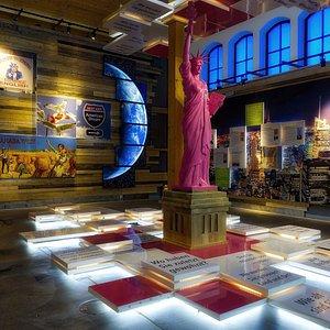 Im Raum der Ankunft erfahren die Besucher mehr über die Umstände der Ankunft der Auswanderer in New York. Mittelpunkt ist die pinkfarbene Freiheitsstatue, die für Freiheit, Aufbruch, Mut steht. Sie signalisiert durch ihre Farbe, dass die Welt bunt ist.