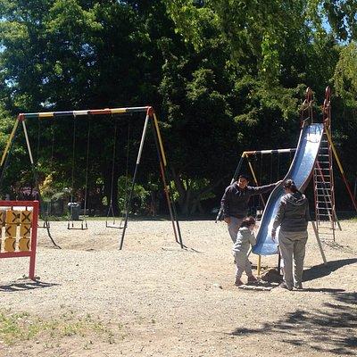 Parquinho público para crianças com balanço, argolas e escorregador.