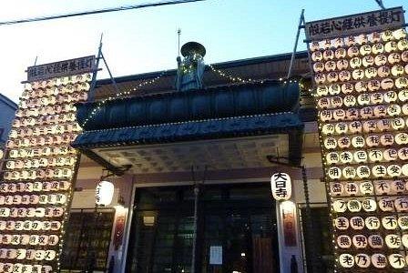 小田急線沿いの通りにあります。お坊様が屋根の上にいます。