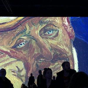 Visiteurs devant une immense reproduction d'une oeuvre du peintre