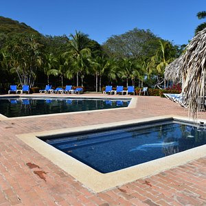 The two pools are located in a large common area of palm trees and grass.  There are several shaded tables to access as well.