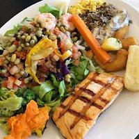 Salmão grelhado, salada, feijão verde, mandioca, camarão empanado, farinha nordestina, purê de aboborá, paçoca e carne com nata.