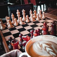para las personas que gustan jugar al ajedrez cuentan con varios tableros en la mesa, para que jugar mientras disfrutas de un delicioso café