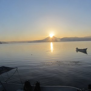 Sunrise over the San Vicente volcano as viewed across Lago de Ilopango with dive boat in foreground.