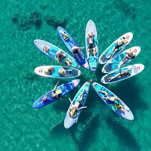 close up drone-view of people relaxing on paddle boards