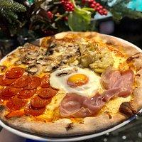 Pizza Quattro Stagioni   Tomato and mozzarella base with Parma ham, pepperoni, artichokes, mushrooms topped  with egg and oregan