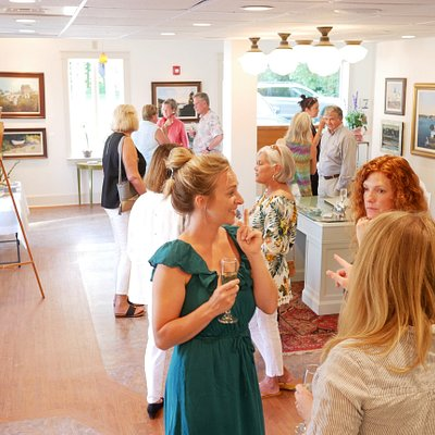 Visitors enjoy some wine, conversation and sally's paintings at the gallery's opening.
