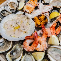 Raw Bar spread w/ fresh scallops, shrimp, crab claws, uni and oysters.