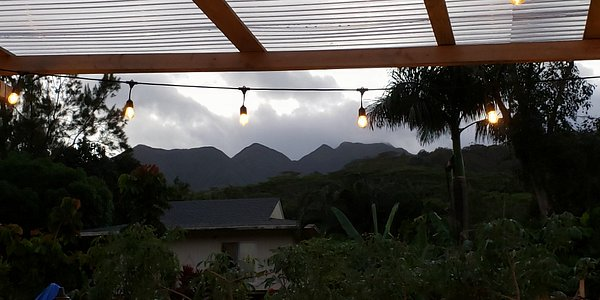 As dusk falls, the view from the pavilion to the mountains