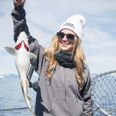 A happy customer showing off her catch and sporting our Tahoe Sport Fishing beanie.