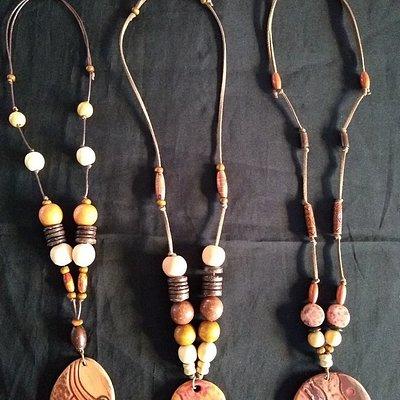 Colares em cerâmica sementes e madeira.
