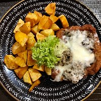 pork chop coated with breadcrumbs with a mixture of cheese and mushrooms, baked potatoes and a serving of salad (three types).