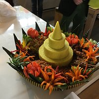 The famous nasi kuning tumpeng served on bamboo woven round tampah