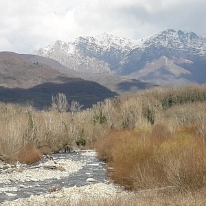 """At the bridge over the Caprio creek, the route shows perhaps the most picturesque view of the day. In the background, the Apennine ridge that separates the Lunigiana from the valley of the Parma river (Emilia region). In particular, the mountains called """"Orsaro"""" and """"Marmagna"""" appear here, covered with fresh snow, which had fallen the day before."""