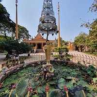 Wat Damnak grounds - Statue of Buddha beneath a parasol or umbrella.  Symbolically, the parasol protects from the heat of suffering, desire, obstacles, illness, and harmful forces.