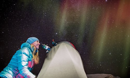 Stargazing under auroras through one of our telescopes, just outside our 40-seat dome theatre