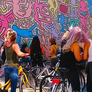 """IL nostro Tour Pisa By Bike, passa da uno dei posti più colorati della città, il murales """"Tuttomondo"""" di Keith Haring."""