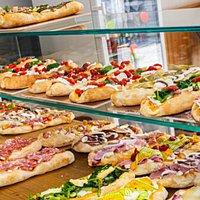 Bancone con le nostre pizze in pala: impasto fragrante e ricche farciture che non vi lasceranno sicuramente delusi