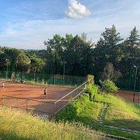Campi da tennis in terra rossa in mezzo al verde sulle colline del Chianti.