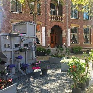 Het vooraanzicht van Museum Sow to Grow met Clipper en planten van bloemen, groenten en kruiden.