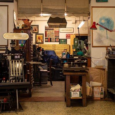 """Panoramica laboratorio tipografico.  A sinistra - macchina da stampa tipografica Heidelberg """"Stella"""" - prodotta dal 1923 e acquisita nel 1967 da Luigino Conte.  A destra - reparto composizione con cassettiere contenenti font tipografici, fregi e componenti di impaginazione appartenenti al periodo storico che va' dal 1800 a fine 1900."""