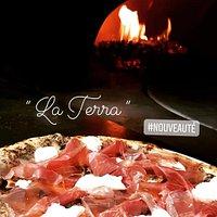 La pizza terra cuisson au bois de hêtre   crème de champignons A la truffes, jambon de parme 22 Mois , mozzarella fior di latte, poêlée de champignions.