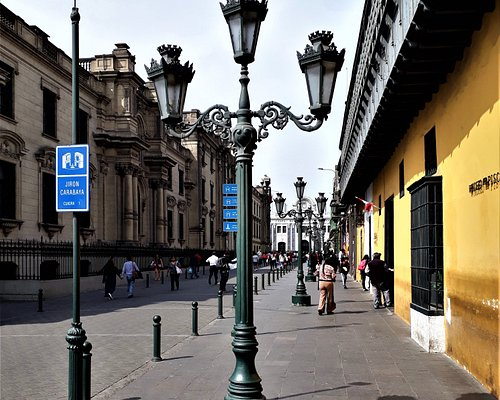 """The lateral yellow wall and the wooden balcony of """"Casa del Oidor"""", as seen at avenue """"Jirón Carabaya"""" in the """"Centro Histórico de Lima""""."""