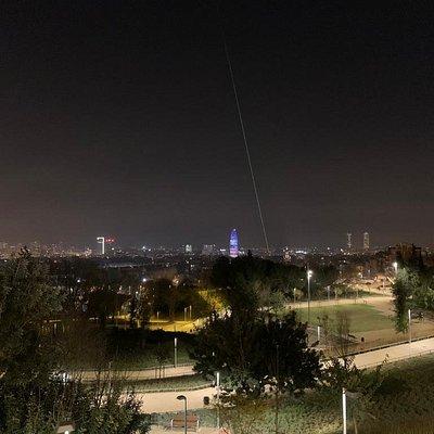 Vista aérea de noche de los Jardines con la ciudad de Barcelona al fondo.