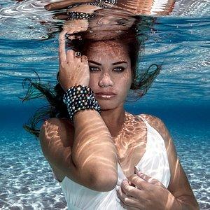 Onaku is wearing a cascade of multicolor tahitian pearls bracelets.  Onaku porte une enfilade de bracelets de perles multicolores de Tahiti.